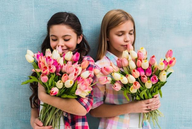 Sonriendo dos chicas de pie contra la pared azul que huele la flor de tulipanes