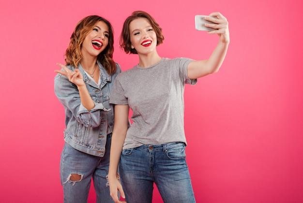 Sonriendo dos mujeres emocionales hacen selfie por teléfono.