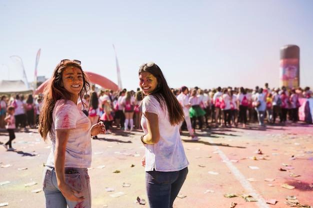 Sonriendo dos mujeres jóvenes disfrutando del festival holi