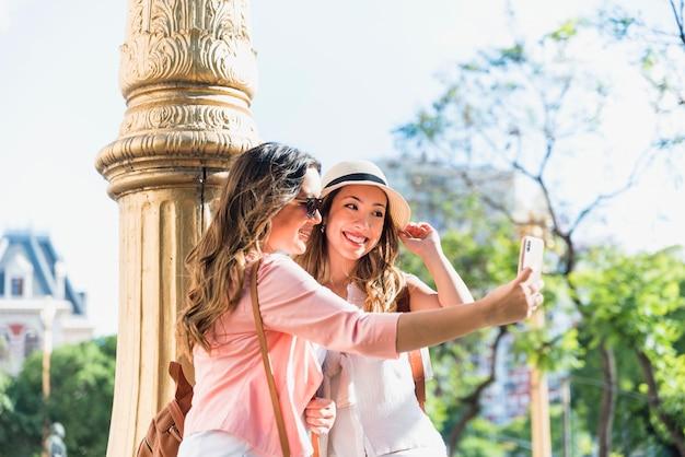 Sonriendo dos turista femenina de pie cerca del pilar hablando selfie desde celular