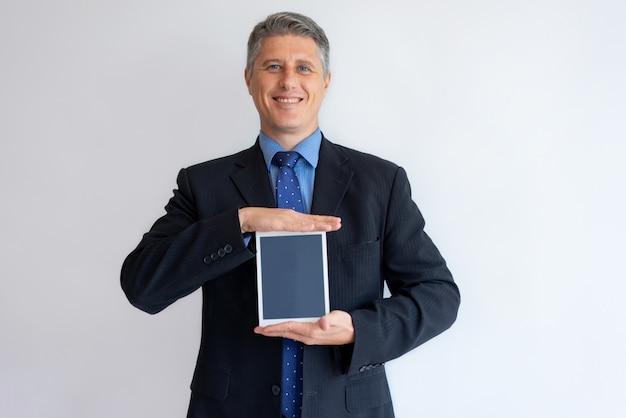 Sonriendo ejecutivo compartiendo información en la pantalla de la tableta