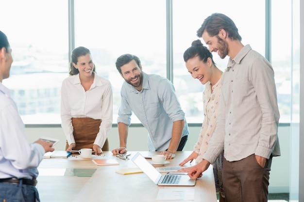 Sonriendo ejecutivos de negocios discutiendo entre sí en la sala de conferencias