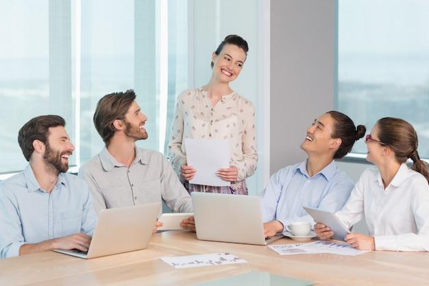 Sonriendo ejecutivos de negocios interactuando entre sí en la sala de conferencias
