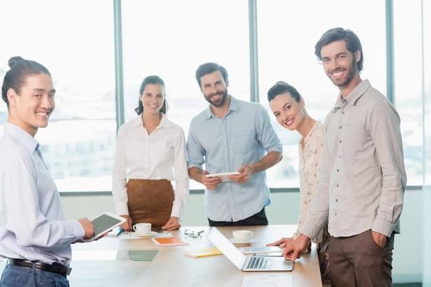 Sonriendo ejecutivos de negocios de pie en la sala de conferencias