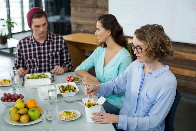 Sonriendo ejecutivos de negocios que tienen comida en la oficina