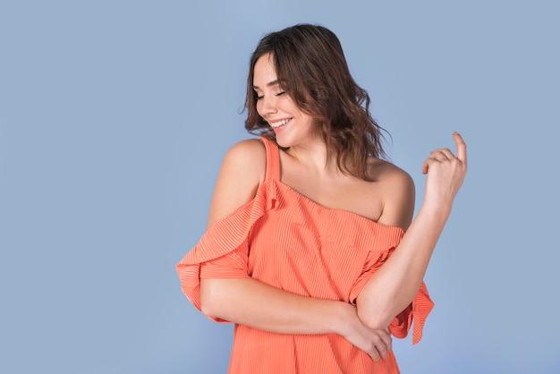 Sonriendo elegante dama en blusa naranja