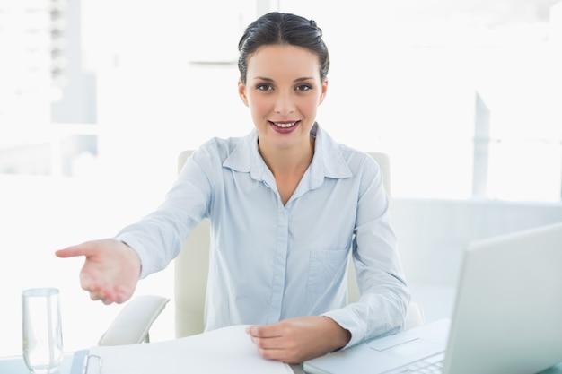 Sonriendo elegante morena empresaria presentando su mano