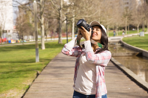 Sonriendo emocionado turista disparando hito