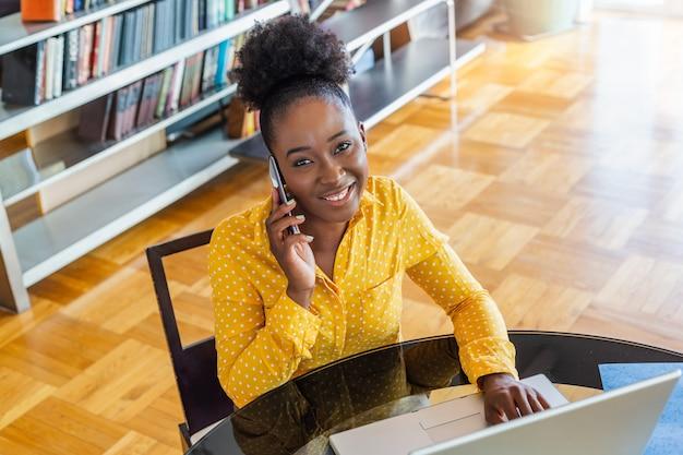 Sonriendo empresaria hablando por teléfono móvil mientras mira a una computadora