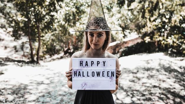 Sonriendo encantador sosteniendo el letrero en el bosque