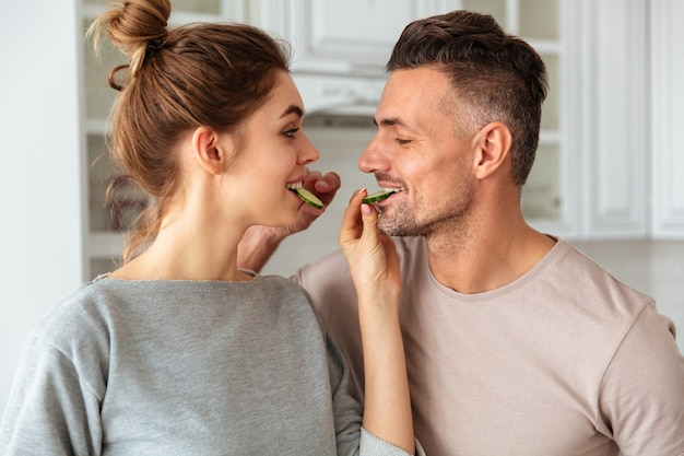 Sonriendo encantadora pareja cocina juntos en la cocina y alimentándose mutuamente