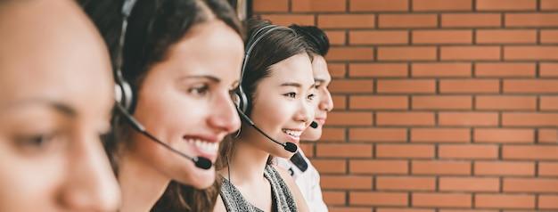 Sonriendo equipo de agente de servicio al cliente de telemarketing multiétnico trabajando en call center