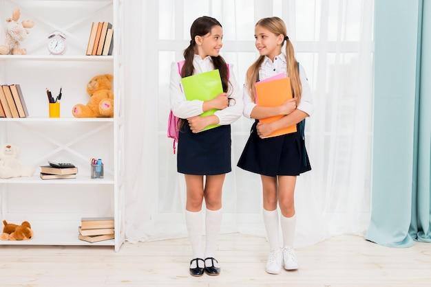 Sonriendo escolares con mochilas de pie en el apartamento y mirando el uno al otro