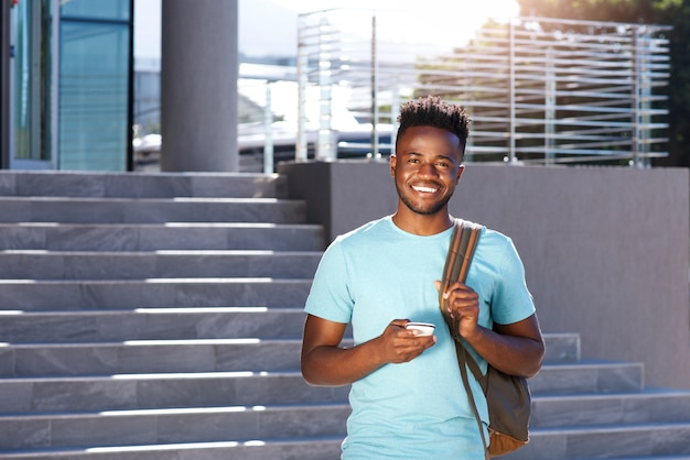 Sonriendo estudiante africano caminando por las escaleras con bolsa y teléfono inteligente