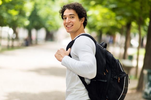 Sonriendo estudiante al aire libre en un patio de la universidad