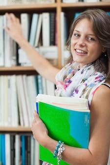 Sonriendo estudiante contra el estante en la biblioteca