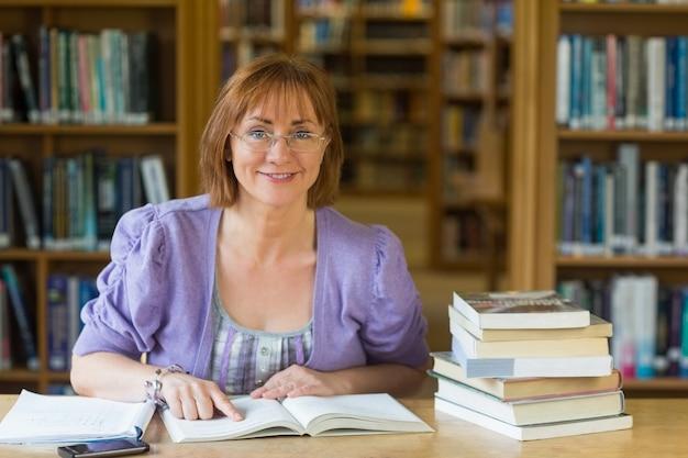 Sonriendo estudiante maduro en el escritorio en la biblioteca