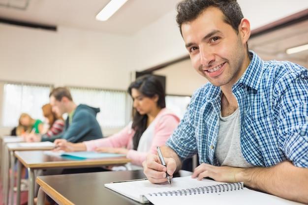 Sonriendo estudiante masculino con otros escribiendo notas en el aula