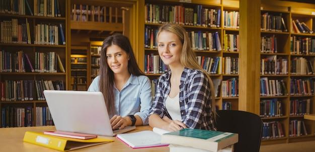 Sonriendo estudiantes usando laptop en biblioteca