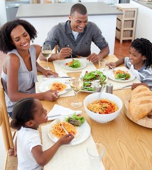 Sonriendo familia cenando juntos