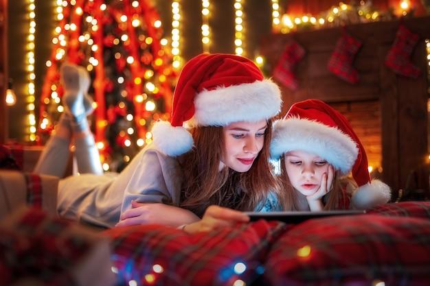 Sonriendo familia madre e hija en santas sombreros y pijamas viendo videos graciosos o eligiendo regalos en tableta digital