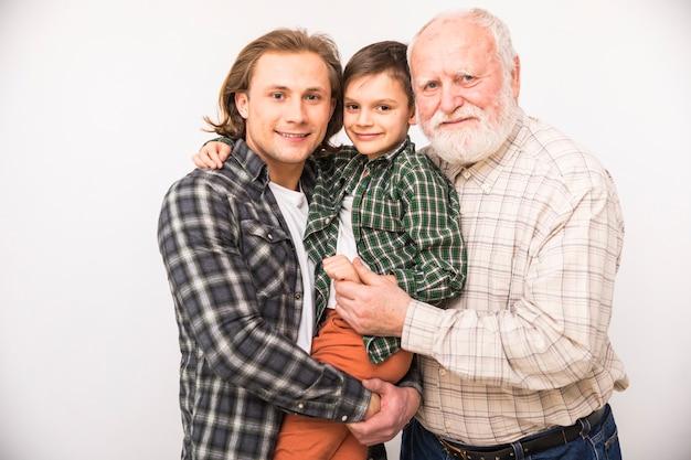 Sonriendo familia multigeneracional mirando a cámara