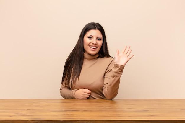 Sonriendo feliz y alegremente, saludando con la mano, dándole la bienvenida y saludándolo, o diciéndole adiós