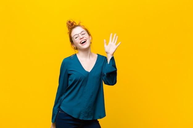 Sonriendo feliz y alegremente, saludando con la mano, dándote la bienvenida y saludándote, o diciéndote adiós