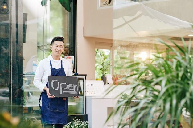 Sonriendo feliz camarero de café de pie en la entrada y mostrando un cartel abierto al dar la bienvenida a los clientes después del cierre