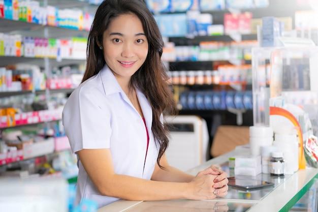Sonriendo y feliz de farmacéutica asiática en la farmacia