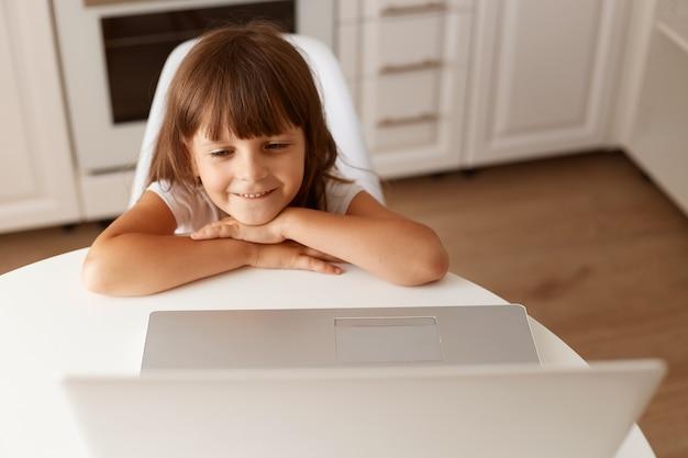 Sonriendo feliz linda niña de cabello oscuro sentado en la mesa, mirando la pantalla del portátil, viendo dibujos animados interesantes, posando en la sala de luz en casa.
