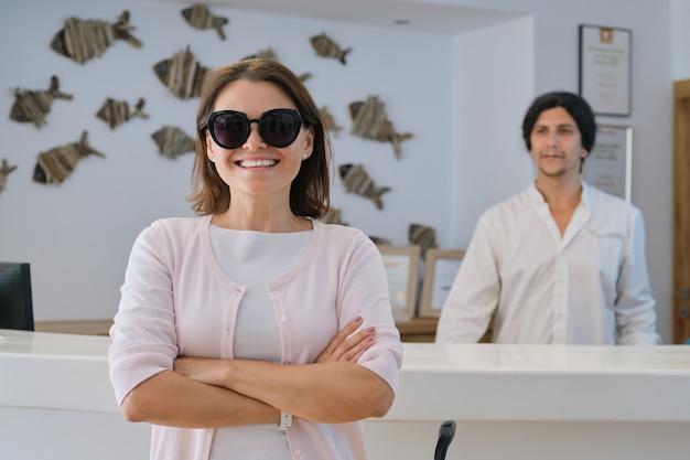 Sonriendo feliz mujer invitada en el vestíbulo interior del resort spa hotel