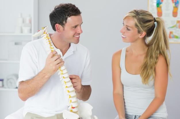 Sonriendo fisioterapeuta mostrando paciente algo en el modelo de esqueleto