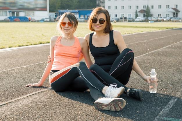 Sonriendo fitness madre e hija adolescente juntos posando en el estadio después de correr