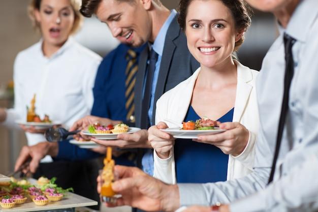 Sonriendo gente de negocios y aperitivos en la tabla buffet