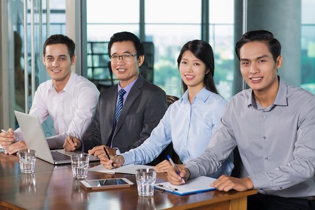 Sonriendo gente de negocios que tienen reunión en la oficina