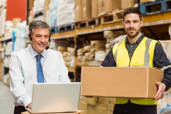 Sonriendo gerente de almacén usando la computadora portátil en un gran almacén
