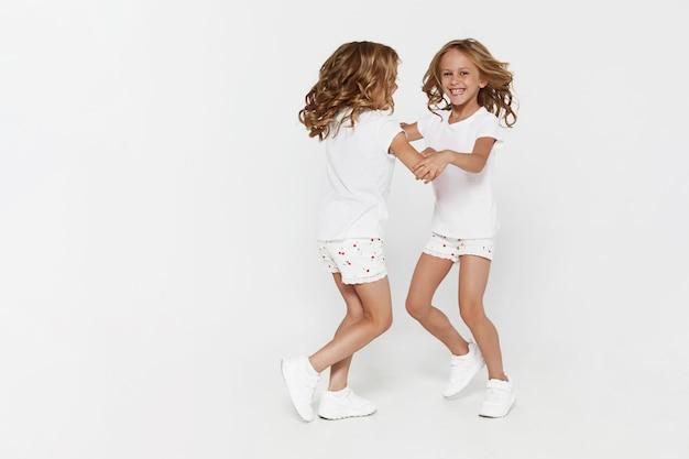 Sonriendo graciosas hermanitas gemelas en ropa blanca bailando