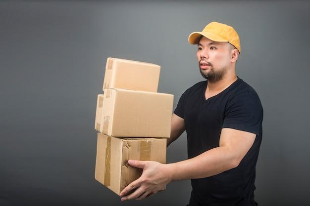 Sonriendo guapo asiático entrega hombre llevaba gorra, dar y llevar paquete, caja de cartón, día de la casa móvil y concepto de entrega urgente