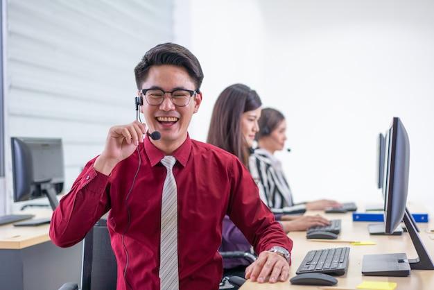 Sonriendo guapo operador de atención al cliente con auriculares trabajando en call center