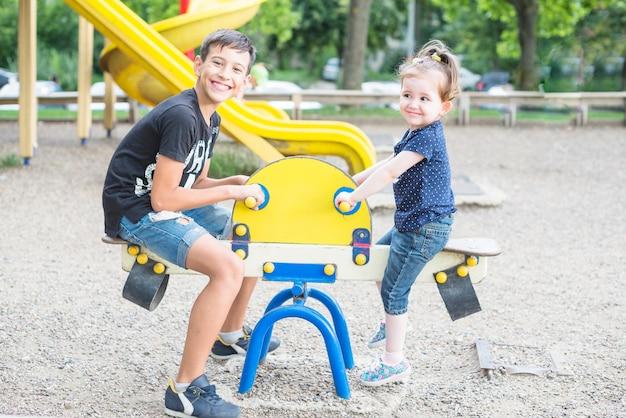 Sonriendo hermano y hermana jugando balancín en el patio de recreo
