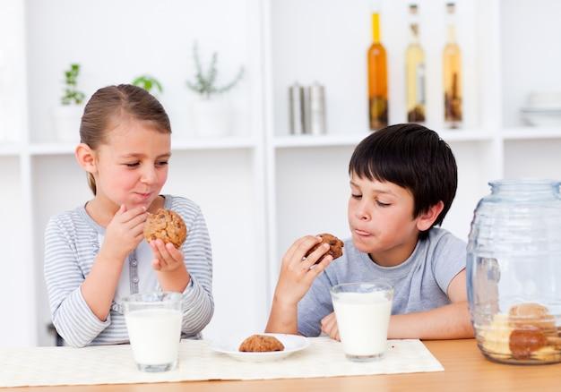 Sonriendo hermanos comiendo galletas