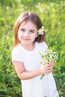 Sonriendo a hermosa chica sosteniendo ramo de flores blancas