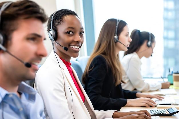 Sonriendo hermosa mujer afroamericana trabajando en call center con equipo diverso