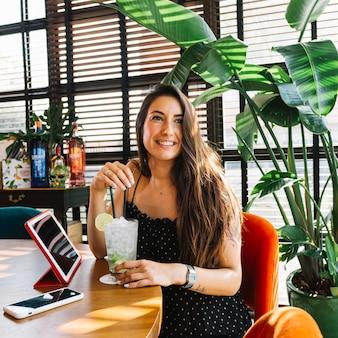 Sonriendo hermosa mujer joven con cóctel; smartphone y tableta digital en el restaurante.
