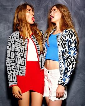 Sonriendo hermosas mujeres jóvenes modelos en tela brillante hipster de verano cerca de la pared gris