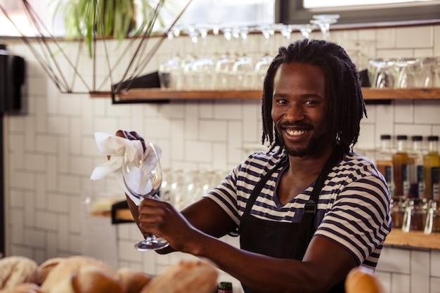 Sonriendo hipster trabajador limpiando gafas