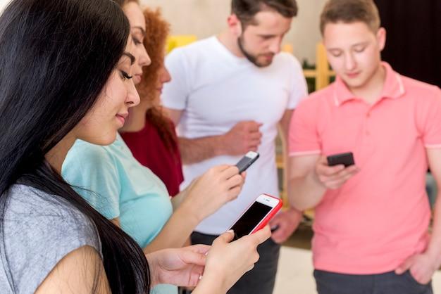 Sonriendo hombres y mujeres usando teléfonos celulares