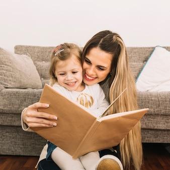 Sonriendo el libro de lectura de madre e hija cerca del sofá