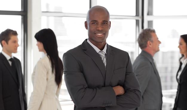 Sonriendo líder empresarial étnica en frente del equipo